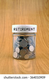 savings concept, coins in jar with retirement label on wooden background.