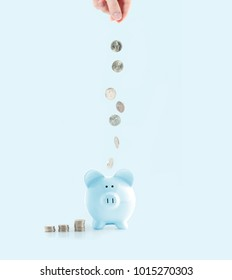 Savings concept. Female hand putting coin into piggy bank on pastel blue background