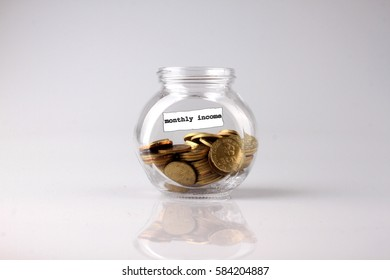 Savings concept: a glass jar with the word MONTHLY INCOME coin Malaysia