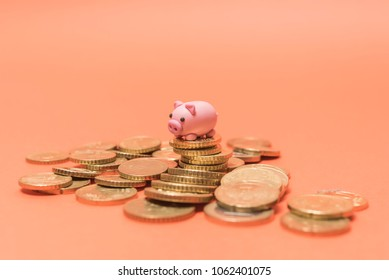 Savings concept. Micro Piggy Bank on top of coins. Money concept. Saving for vacation. Home Finance concept.
