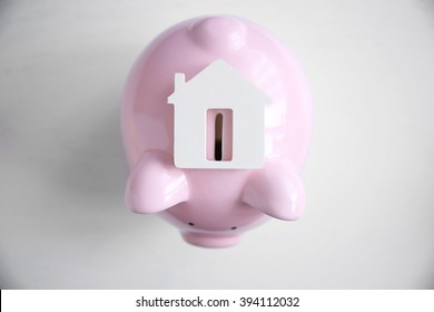 Savings concept. Piggy bank with house figure on white table, close up