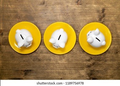 Savings consumer concept. Three dinner plates with piggy banks on the table