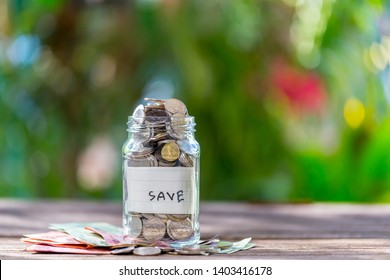 Savings deposit coins in a clear glass bottle, on a wooden floor with bokeh in the background.