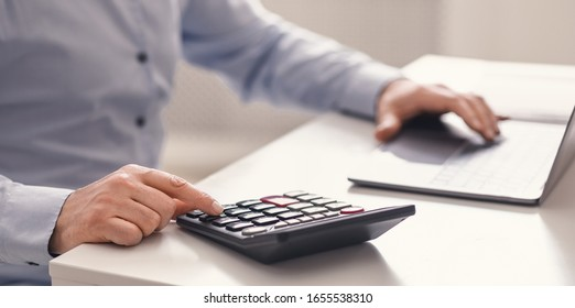 Savings, Finances And Economy Concept. Mature man with counting money using calculator and laptop computer