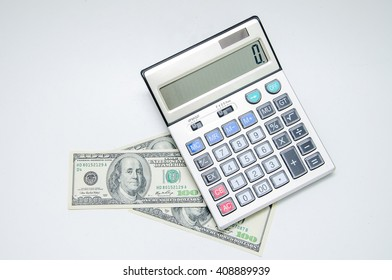 Savings, finances and economy concept. Money and the calculator on a light table.