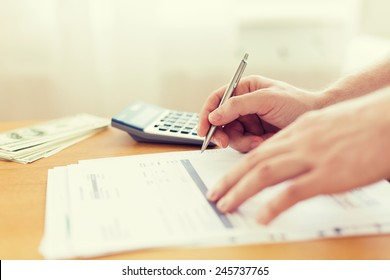 savings, finances, economy and home concept - close up of man with calculator counting money and making notes at home