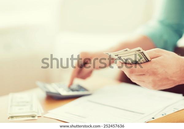 貯蓄、財政、経済、家庭のコンセプト – 計算機と接写(家庭での計算、メモ作成)