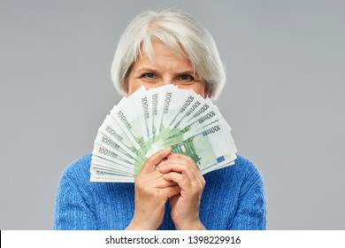 savings, finances and people concept - senior woman hiding face behind fan of hundred euro money banknotes