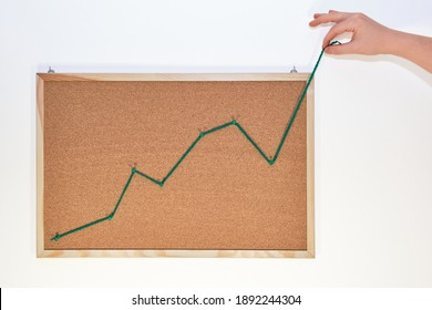 Savings, investment and off the charts concept. Hand pulling the line of a growing graph outside the cork board.