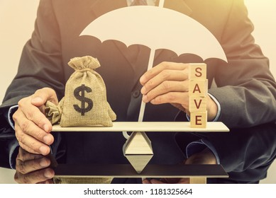Savings protection / keep money safe concept : Businessman holds a white umbrella protects or guards a dollar money bags on a balance scale, depicts protection when bank or building society goes bust.