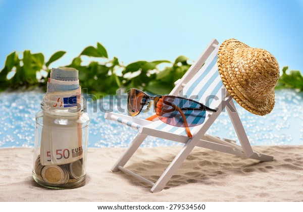 Savings for vacation, glas with money bills and coins at the beach