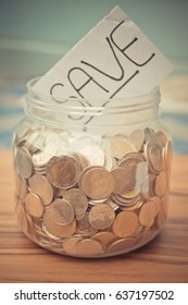 savings word with coin in glass jar on wood table