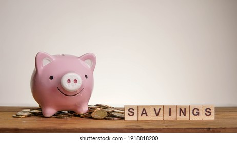 Savings wording with piggy bank with coins money on wooden table against beige background
