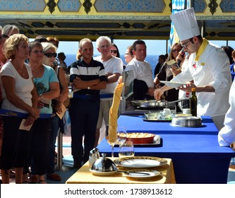 Savona/Italy- Ocober 13 2013 people looking on a cheif which cooks food on a small kitchen