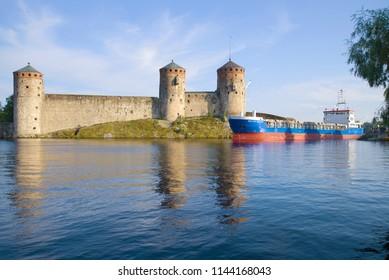 "SAVONLINNA, FINLAND - JULY 24, 2018: Cargo ship ""Baltic Sailor"" passes through the strait near the Olavinlinna fortress"