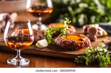 Savory beef steak tartare served with egg yolk, garlic and herbs on a wooden desk. Whiskey as a beverage.