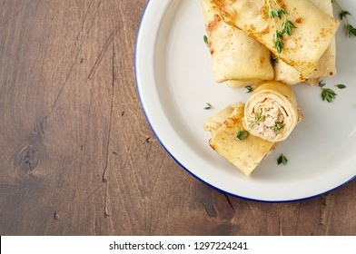 Savory crepe rolls with ground meat filling. Traditional Russian Shrovetide Maslenitsa festival meal on wooden background. Close up top view with copy space