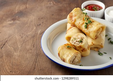 Savory crepe rolls with ground meat filling served with fresh thyme, sour cream and tomato sauce. Traditional Russian Shrovetide Maslenitsa festival meal on wooden background