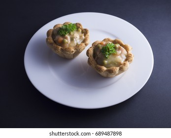 Savory Danish tartlets (tarteletter) made from puff pastry, filled with a creamy chicken, asparagus and carrot sauce. Placed on white plate and isolated on black background