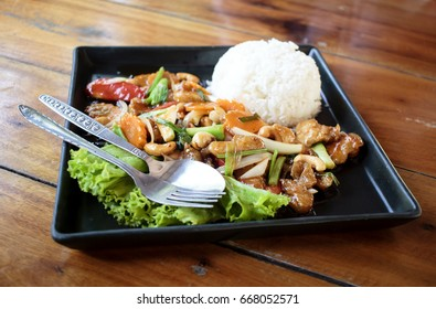 Savory dish in Thailand - chicken meat fried with veggies and cashew nuts served with rice and salad.