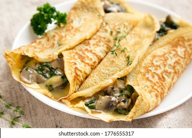 Savory Homemade Mushroom, Spinach and Cheese Crepes on a white plate, side view. Close-up.