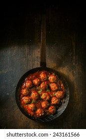 Savory meatballs in a piquant spicy sauce garnished with fresh herbs, overhead view in a frying pan or skillet on a rustic wooden table