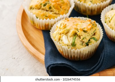 Savory muffins with feta cheese and spinach on a wooden plate on a white stone backdrop.
