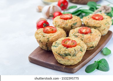 Savory muffins with quinoa, cheese and spinach topped with tomato, on a wooden board, horizontal, copy space
