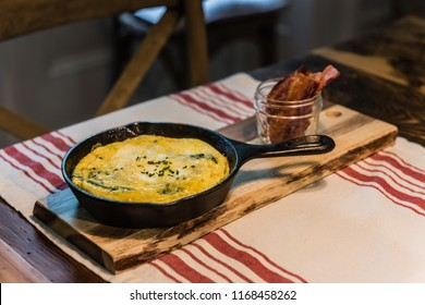 Savory omelette presented in iron skillet and bacon served upright in mason jar.