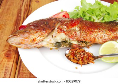 savory on plate : roast golden fish served on fish plate with lemon tomatoes and spices
