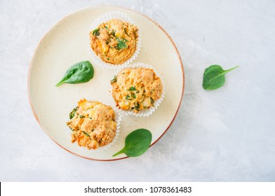 Savory potato spinach and feta muffins served on a plate. White stone background. Top view.