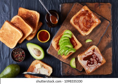 savory toasts for breakfast with butter, avocado slices and healthy food spread made from leftover brewers yeast extract with vegetables and spices, view from above, flat lay