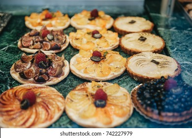 Savory various fruit date, pear, peach and blackberry tartelette desserts displayed in a French patisserie vitrine