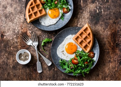 Savory waffles, fried eggs and arugula, cherry tomato salad - delicious healthy breakfast on wooden background, top view