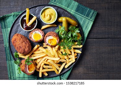 Savoury scotch eggs - british party food of soft boiled eggs wrapped in sausage meat and breadcrumbs and then deep-fried, served on a black plate with pickles, french fries, top view, close-up