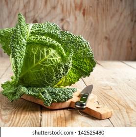 Savoy cabbage on wooden background
