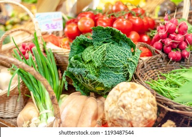 Savoy cabbage and other fresh vegetables for sale in a Parisian food market at the Marche rue d'Aligre