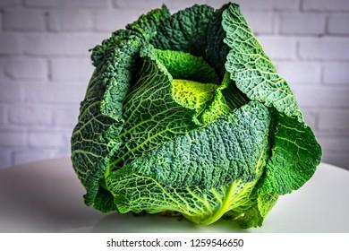 Savoy cabbage, white brick wall background