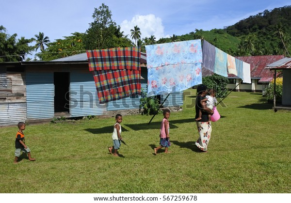 SAVUSAVU, FIJI - JAN 23 2017:Indigenous Fijian woman and children in a local village in Vanua Levu Island, Fiji. The Fijian woman generally supervises the house keeping and disciplines the children