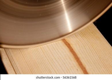Saw blade ripping through wodden board