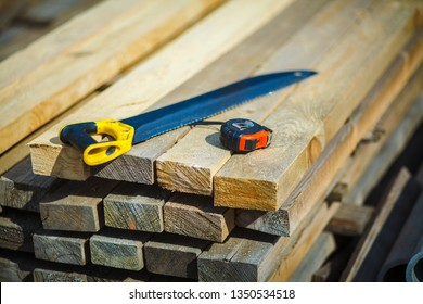 Saw with a construction tape measure on wooden boards. Wooden planks. Beams. Air-drying timber stack. Wood air drying (seasoning lumber or wood seasoning). Timber. Lumber.