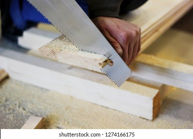 a saw cuts wooden boards, which is in the hand of a man, the concept of repair, construction, natural materials