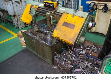 Saw cutting tool steel bar by automatic feed and a pile of scrap metal