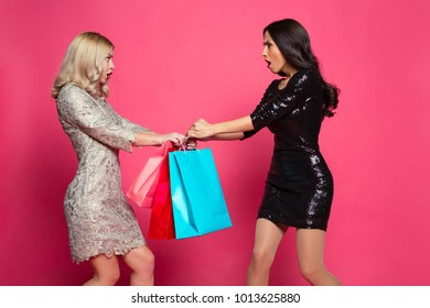 I saw this first! Shopping concept. Two young women quarrel and tear out shopping bags on a pink background.
