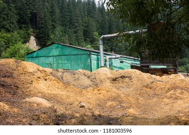 Sawdust piles at lumberjack factory in the mountains, cut down trees near pine forest countryside, deforestation concept, ecological catastrophy concept