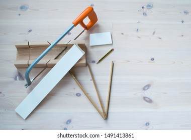Sawing baseboards using a miter box and a measuring stick, on a wooden floor.