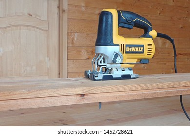 Sawing wooden board  with power jigsaw. Construction of country cottages, power tools, carpentry wood works