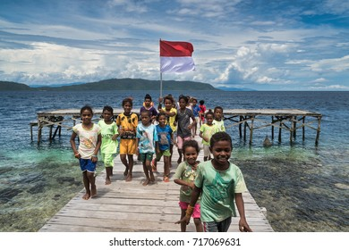 Sawinggrai village, Raja Ampat, West Papua, Indonesia - August 7, 2017 : Cheering kids with the Indonesian flag on the jetty of the village