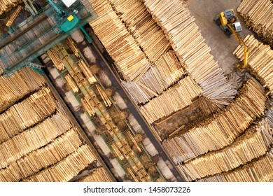 Sawmill aerial view chopped tree wood logs stacks in a row with machinery