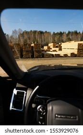 Sawmill from a car window. Warehouse for sawing boards on a sawmill outdoors. Timber mill: storage of planed wooden boards.
